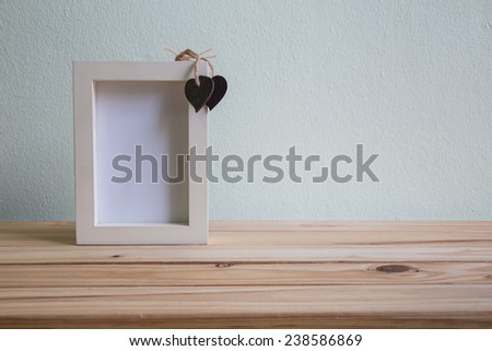 White photo frame on wooden table over grunge background, Valentine concept - stock photo