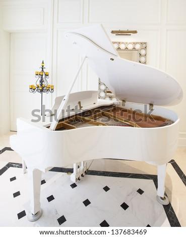 White piano in white room - stock photo