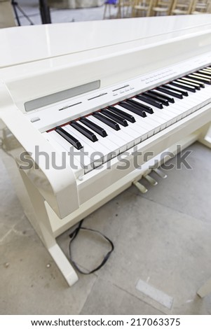 White piano on stage, detail musial instrument of classical music - stock photo