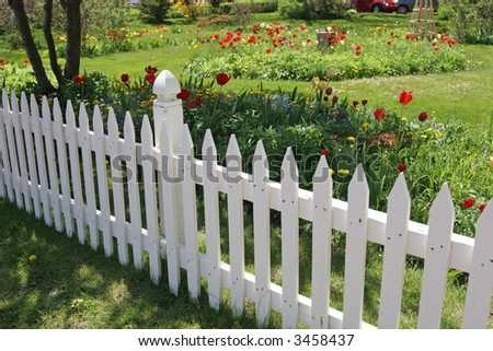 White picket fence along side a perennial flower garden