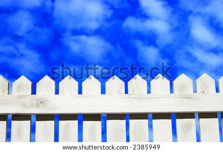 White picket fence and blue sky - stock photo
