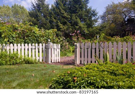 White picket fence and gate frame the entrance to a kitchen garden overflowing with produce - stock photo
