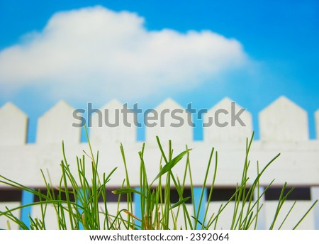 White picket fence and sky with green grass - stock photo
