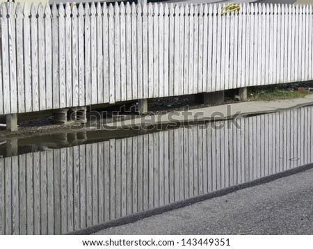 White picket fence reflected by puddle along pavement on city street