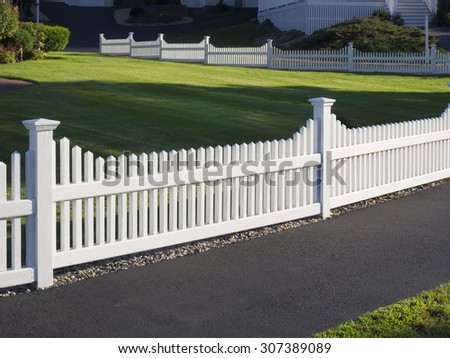 White picket fence that delineates the grass from the pathway
