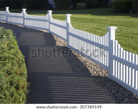 White picket fence that delineates the grass from the pathway - stock photo