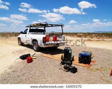 White pickup truck with construction equipment at a desert construction site. Horizontally framed photo. - stock photo