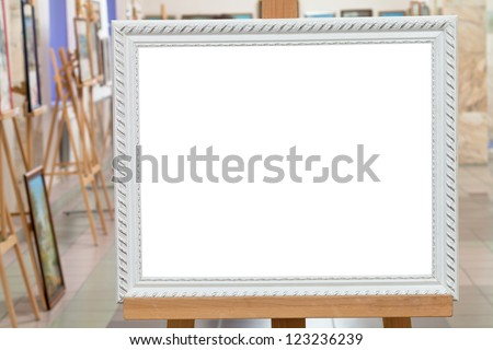 white picture frame with white cut out canvas on easel in art gallery hall - stock photo