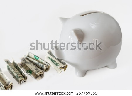 White piggy bank eating USA dollars one at a time, financial concept, saving one dollar at a time. Image over white background  not isolated - stock photo