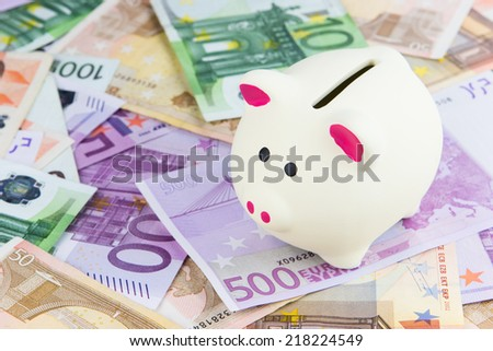 white piggy bank placed on Euro banknotes, concept for cut in interest rates, euro crisis, saving
