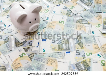 White piggy bank surrounded by five Euro notes - stock photo