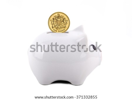 White piggy bank with British pound coin in the slot. Concept of saving for a rainy day, education, retirement, etc. Isolated on White.