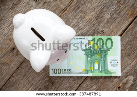 White piggy bank with 100 euro on wooden surface. Top view. - stock photo
