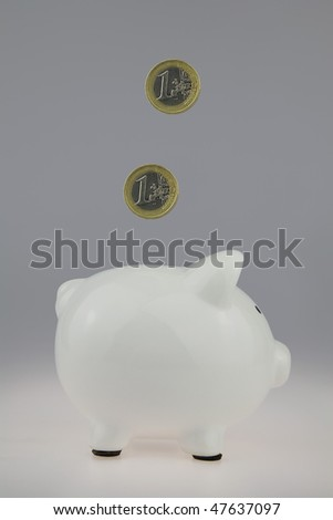 White Piggy bank With One Euro Coins falling from above and heading for the money slot,