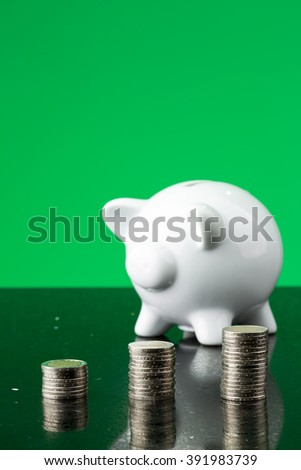 White piggy bank with stack of coins - stock photo