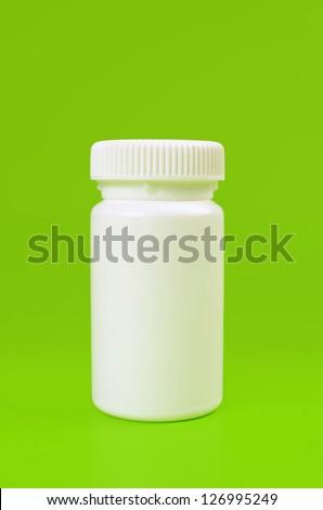 White pill bottle on green background - stock photo