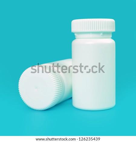 white pill bottles on blue background - stock photo