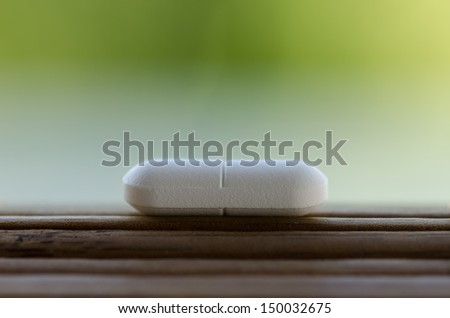 White pill on wooden surface - stock photo