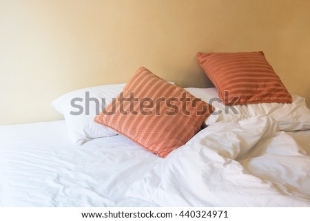 white pillow and orange pillow on bed and with wrinkle messy blanket in vintage bedroom, from sleeping in a long night winter. - stock photo