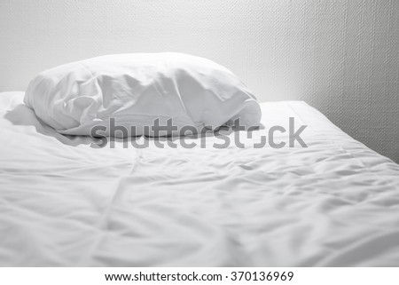 White pillow lying on the empty bed - stock photo