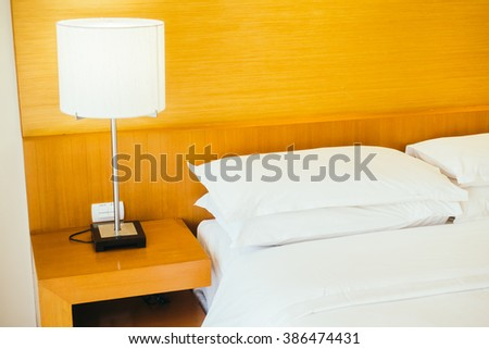 White pillow on bed with light lamp decoration interior of bedroom - Vintage light Filter
