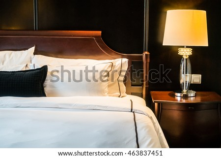 White pillow on bed with table light lamp decoration in bedroom interior
