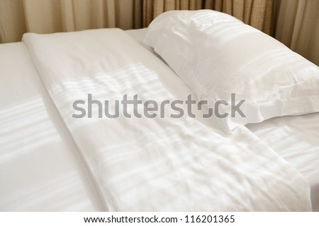 White pillows and bed in bedroom. - stock photo