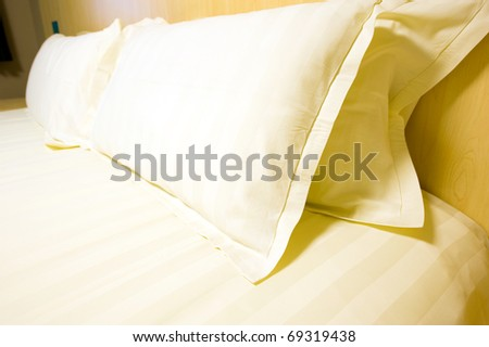 White pillows and bed in white bedroom - stock photo