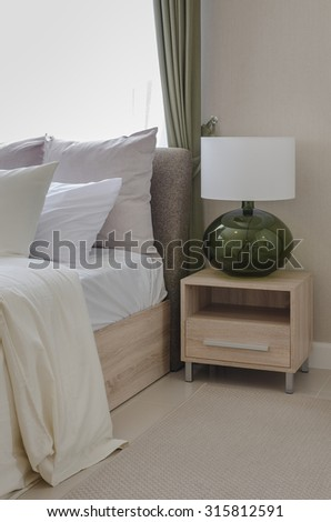 white pillows on bed with modern white lamp on wooden table side in modern bedroom