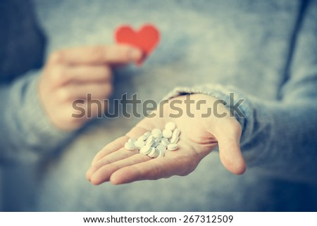 White pills and paper heart in hands. Medicine and health care concept. Toned image - stock photo