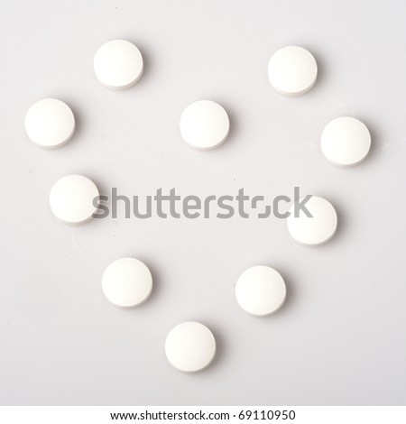 White pills form heart shape isolated on grey background - stock photo