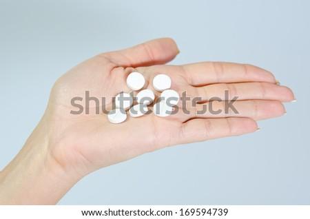 white pills in hand - stock photo