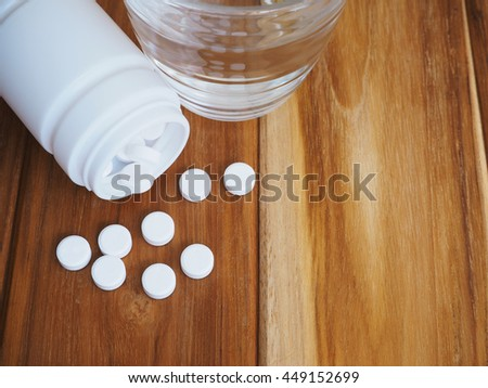 White pills medicine and glass of water on wooden background - stock photo