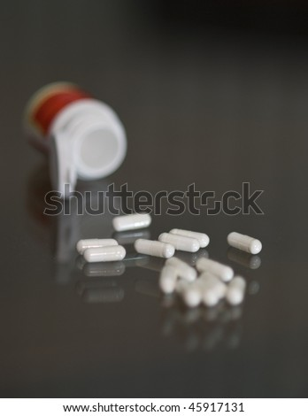 White pills on a glass table.