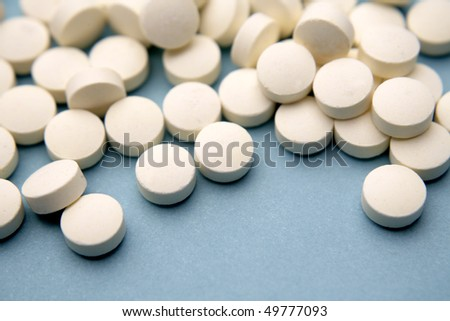 White pills on blue background - stock photo