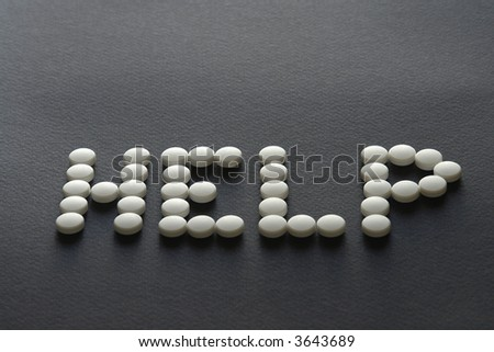 White pills on dark background, make word help