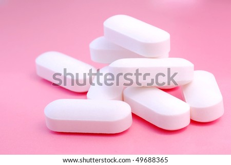 White pills on the pink background