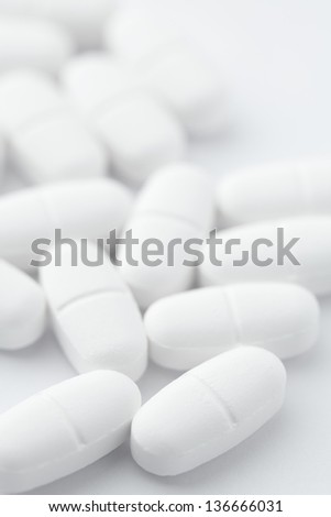 White pills on white background - stock photo