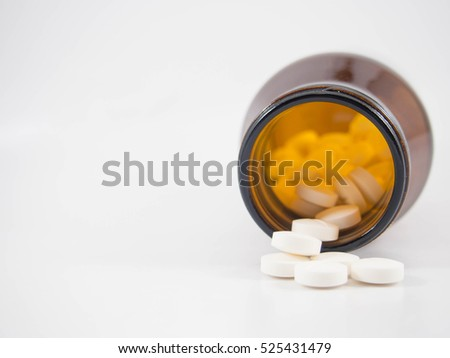 White pills or tablets spilling out of brown glass bottle on white background. Medication concept. Copy space.
