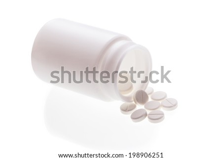 White pills spilled on white background - stock photo