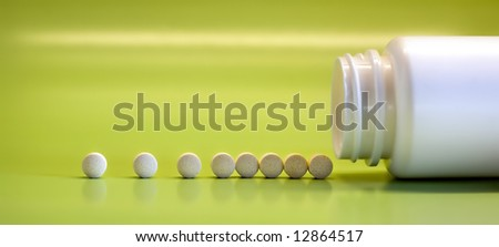 White pills spilling from the bottle - stock photo
