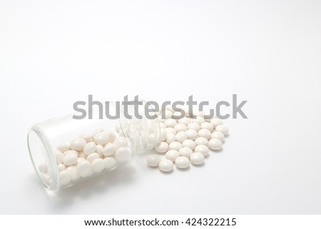 White pills spilling out of a  transparent medicine bottle on white background.