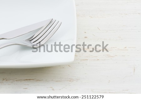 White place setting on a shabby white table - stock photo