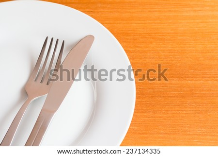 White place setting on wooden table - stock photo