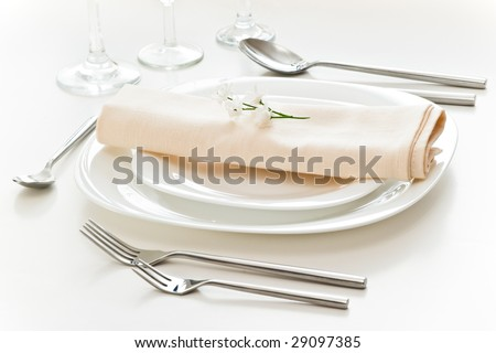 white place setting with beige napkin - stock photo