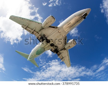 White plane flies in the blue and cloudy sky. Bottom view of aircraft.