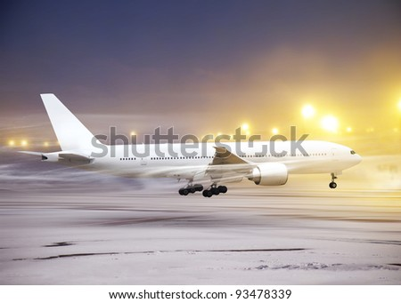 white plane in airport at non-flying weather, snow-storm - stock photo
