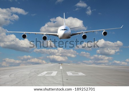 White plane makes a low pass over the airport runway - stock photo