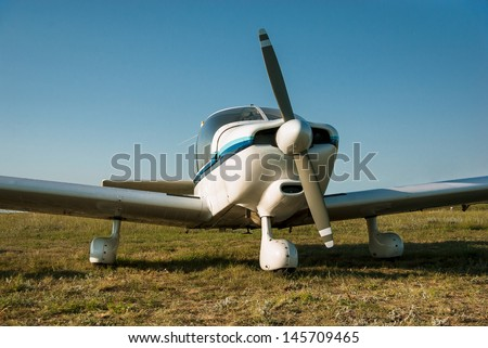 White plane - propeller, wings and fuselage of the aircraft. Retro airplane at the airfield. Aviation transport - travel on sky. - stock photo