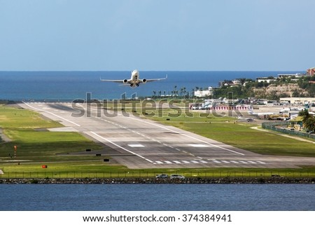 White plane take off above the ocean - stock photo